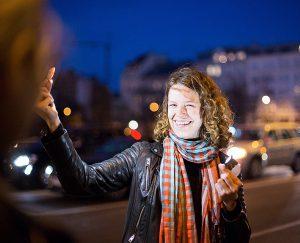 lachende Frau vor Staße beleuchtet sich mit kleinem Scheinwerfer als Vorführeffekt beim Fotokurs Wien mal anders