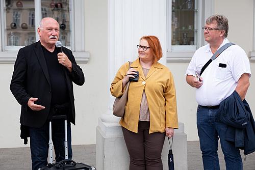 Fotografie Inspirationen. Lois Lammerhuber steht neben zwei Fotokursteilnehmern uns spricht in ein Mikrofon.