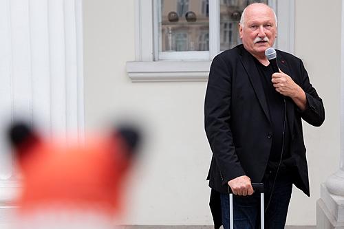 Fotografie Inspirationen. Direktor Lois Lammerhuber steht vor dem Arnulf Rainer Museum und spricht in ein Mikrofon. Finn der Fotofuchs im Vordergrund.