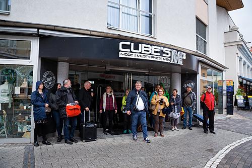 Fotografie Inspirationen. Eine große Gruppe an Kursteilnehmern stehen unter einem Vordach eines Geschäfts in einer Einkaufstraße und suchen Schutz vor einem Regenschauer.