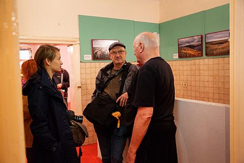 Fotografie Inspirationen. Kursteilnehmer in einem Ausstellungsraum unterhalten sich mit dem Direktor der Ausstellung Lois Lammerhuber.